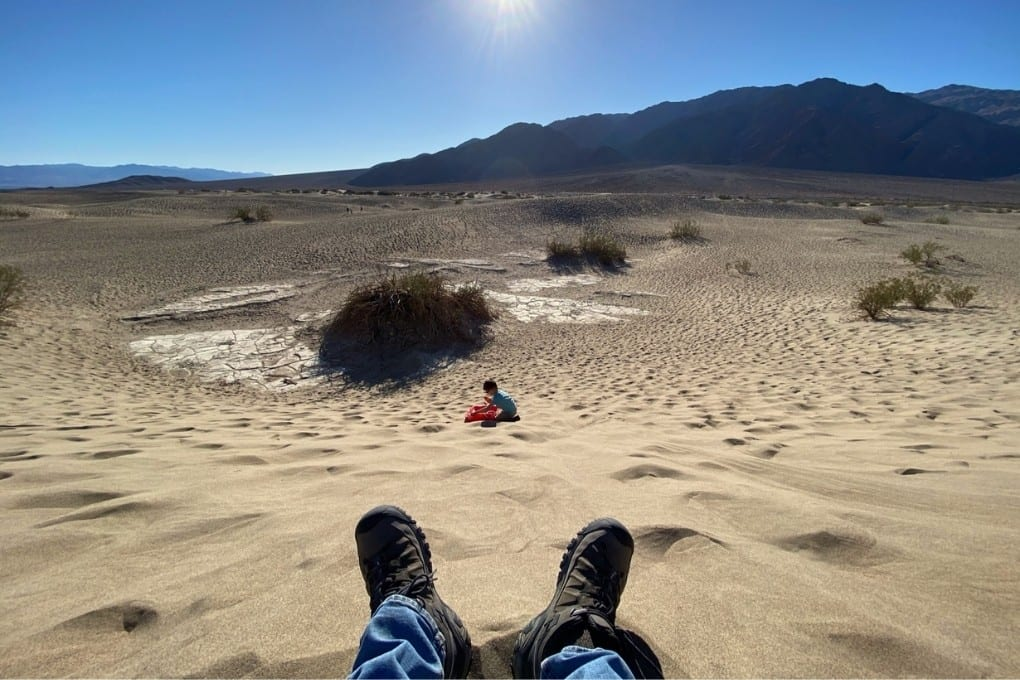 John's feet getting ready to sled the sand dunes, Mesquite Sand Dunes in Death Valley National Park