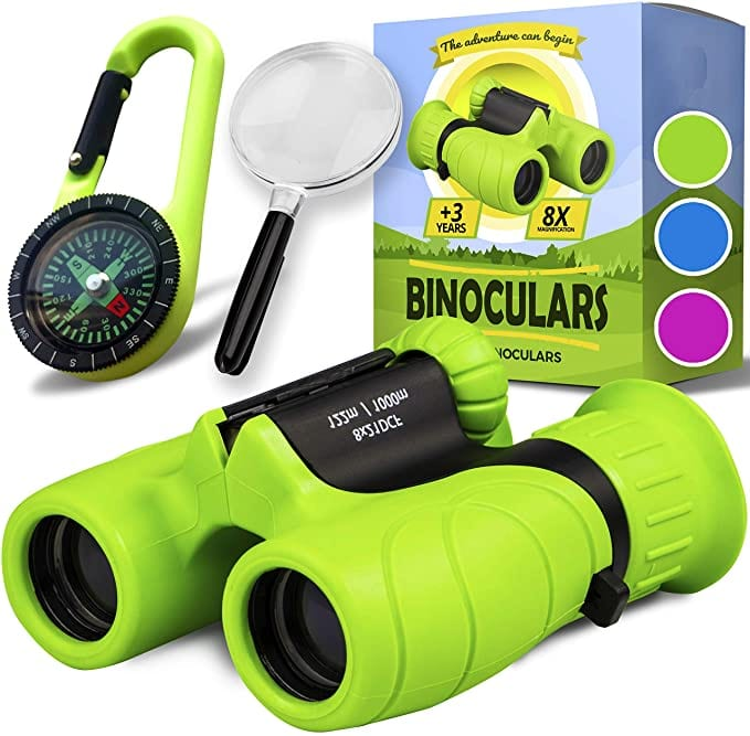 Promora Binoculars for Kids in green, photographed with box, magnifying glass, carabiner, and compass