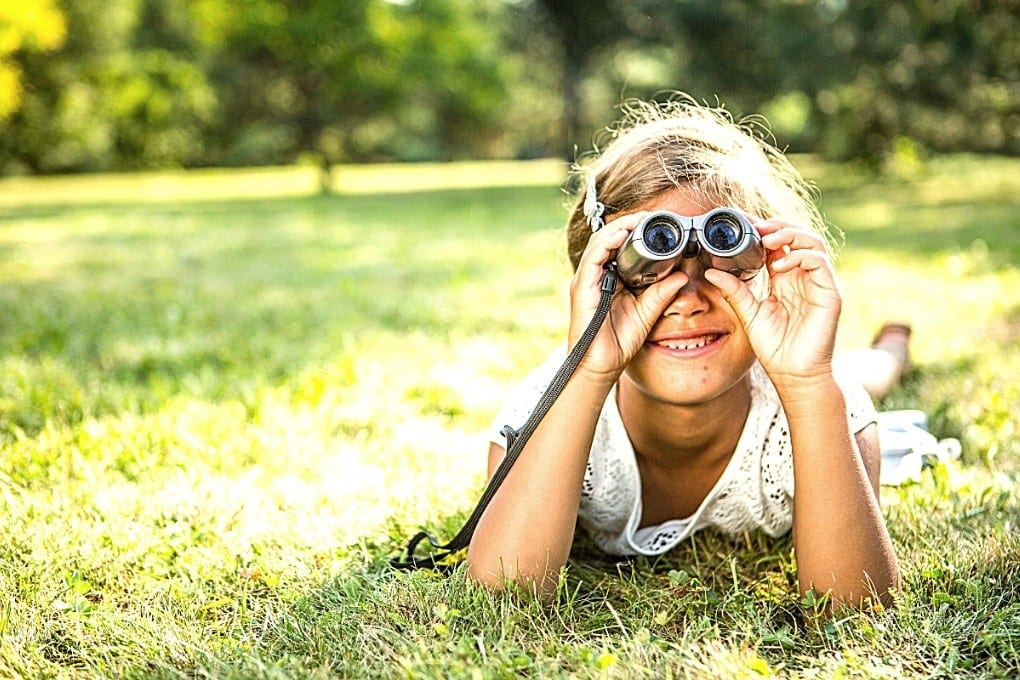 Girl laying in the grass using smaller scale binoculars