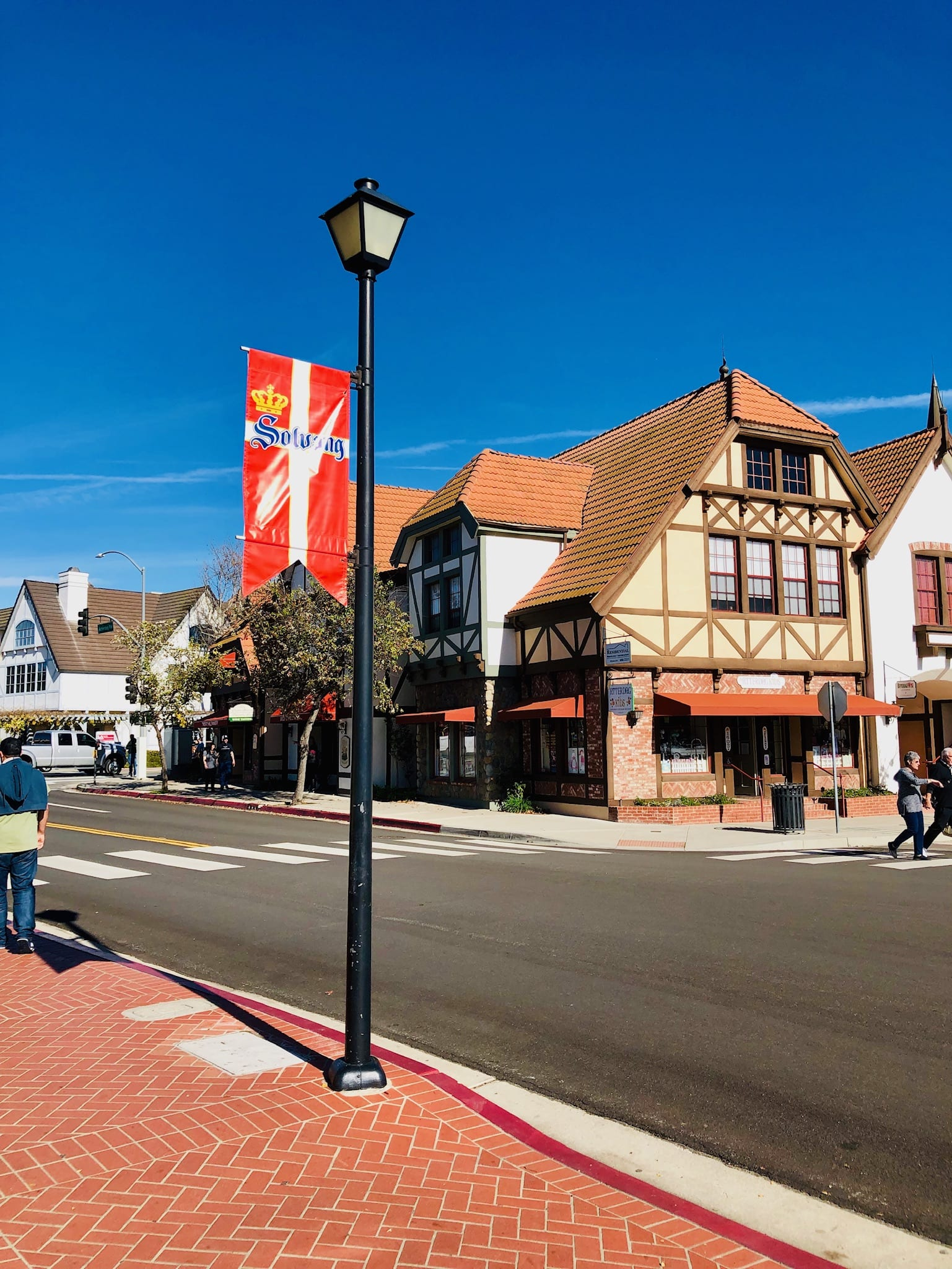 Image of Solvang Flag on Lamp Post, buildings in Danish architectural style in the background