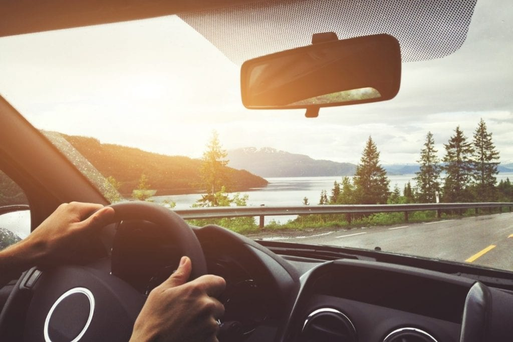 Hands on the wheel with a mountain lake through the windshield.