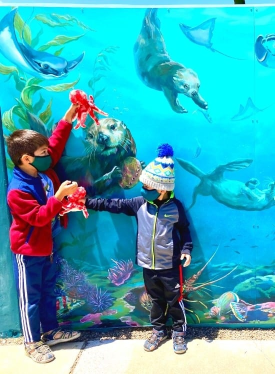 JJ and Bug playing with their new octopus stuffies in front of the underwater mural outside the Central Coast Museum
