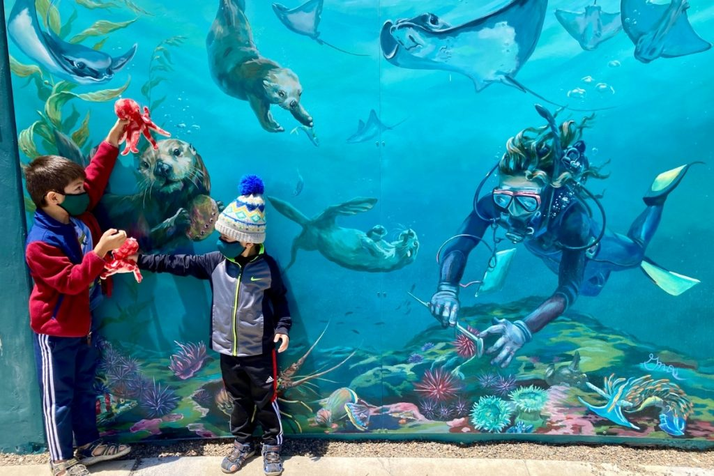 Boys playing in front of the underwater mural outside of the Avila Beach Aquarium