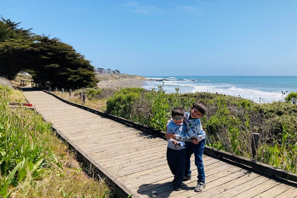Boys playing on the boardwalk in front of Moonstone Beach, another great road trip stop on Highway 1 with kids.