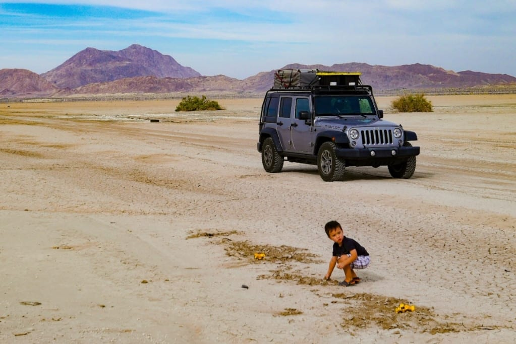 Image of a jeep in the desert with a young child in the foreground