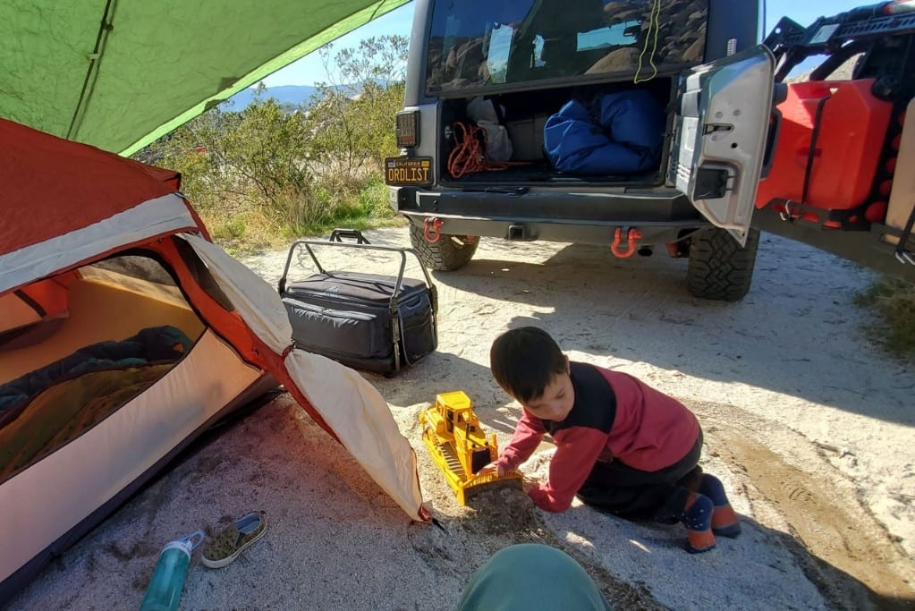 Photo of an overlanding camping set up with the author's son playing