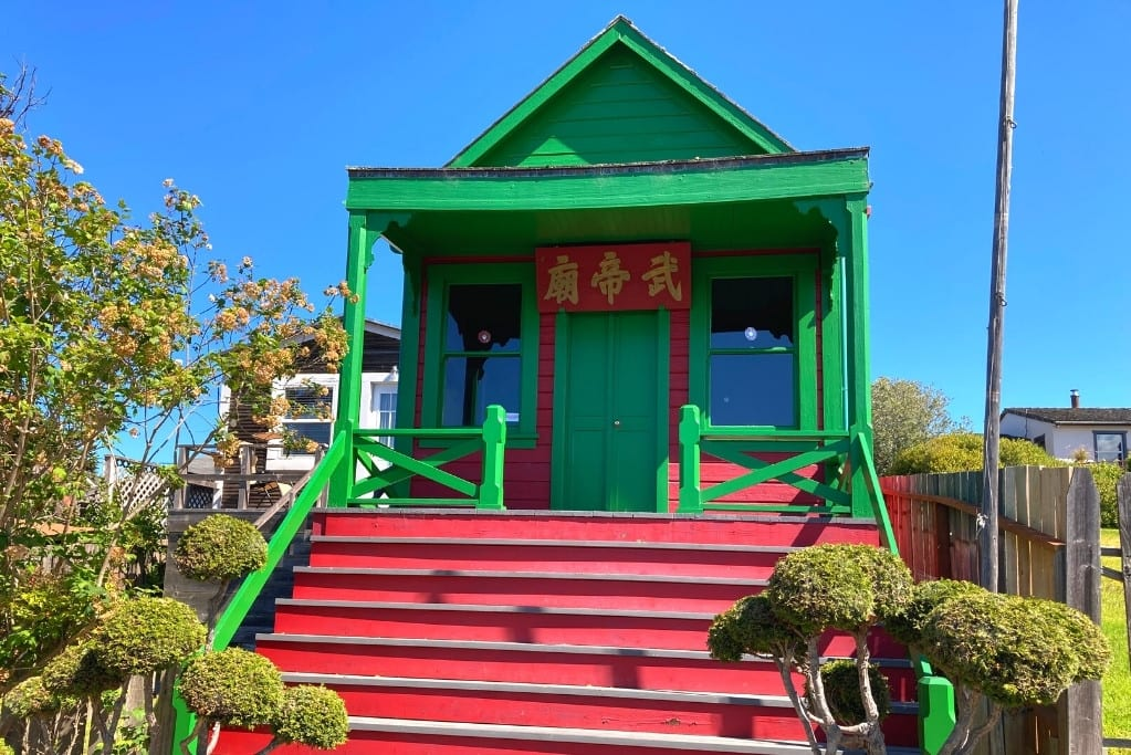 The facade of the Temple of Kwan Tai is bright red and green. It both stands out and blends in with its neighbors in this historic landmark district.
