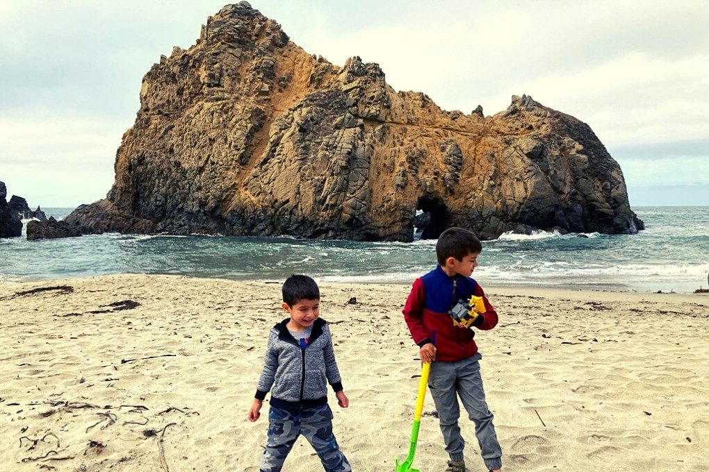Boys Playing in front of Keyhole Arch at Pfeiffer Beach, Big Sur